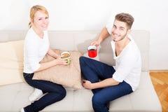 Молодые пары говоря на софе Стоковые Фото