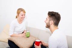 Молодые пары говоря на софе Стоковое Фото