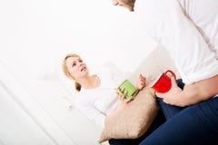 Молодые пары говоря на софе Стоковые Изображения RF