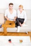Молодые пары говоря на софе Стоковая Фотография RF