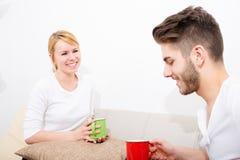 Молодые пары говоря на софе Стоковая Фотография