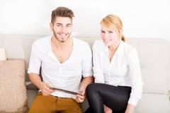 Молодые пары говоря на софе Стоковое Изображение RF