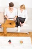 Молодые пары говоря на софе Стоковые Изображения