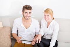 Молодые пары говоря на софе Стоковое Изображение