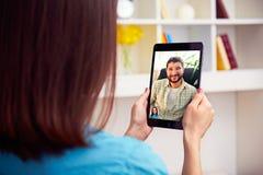 Пары говоря он-лайн видео- бормотушк стоковая фотография