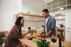 Молодые пары говоря пока варящ в кухне Стоковые Фото