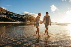 Молодые пары гуляя на береге моря Стоковое Изображение