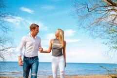 Молодые пары гуляя на пляж пары любят романтичное Стоковые Изображения