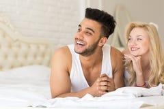 Молодые пары лежа в кровати, человеке счастливой улыбки испанском и любовниках женщины в спальне Стоковые Изображения