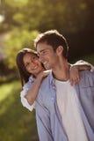 Молодые пары держа каждое другое в парке Стоковое Изображение