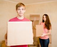 Молодые пары держа картонные коробки для двигать в новый дом Стоковые Изображения