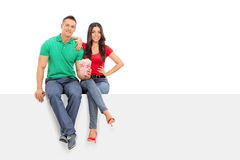 Молодые пары держа попкорн усаженный на панель Стоковые Фотографии RF