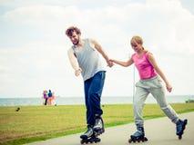 Молодые пары держа руки пока rollerblading Стоковое Фото