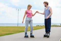 Молодые пары держа руки пока rollerblading Стоковые Фото
