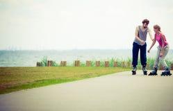 Молодые пары держа руки пока rollerblading Стоковая Фотография