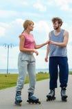 Молодые пары держа руки пока rollerblading Стоковое Изображение