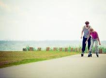 Молодые пары держа руки пока rollerblading Стоковое Изображение RF