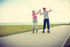 Молодые пары держа руки пока rollerblading Стоковые Изображения