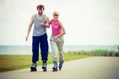 Молодые пары держа руки пока rollerblading Стоковые Изображения RF