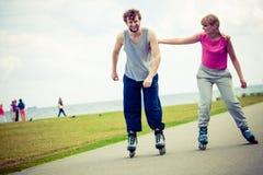 Молодые пары держа руки пока rollerblading Стоковые Фотографии RF