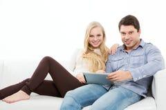 Молодые пары держа сенсорную панель Стоковые Фото