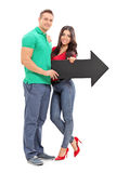 Молодые пары держа стрелку указывая справедливо Стоковое фото RF