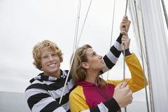 Молодые пары держа такелажирование на паруснике Стоковые Изображения RF
