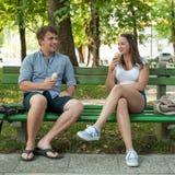 Молодые пары есть мороженое в тени на стенде в парке на ho Стоковые Изображения RF