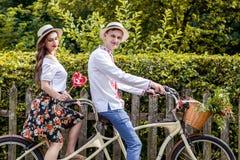 Молодые пары ехать тандем велосипеда в парке Стоковые Фотографии RF