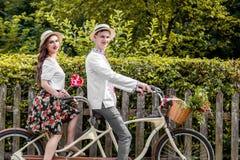 Молодые пары ехать тандем велосипеда в парке Стоковое фото RF