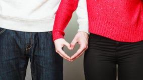 Молодые пары делая форму сердца руками Стоковая Фотография