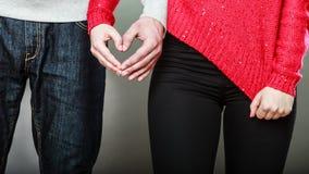 Молодые пары делая форму сердца руками Стоковые Изображения RF