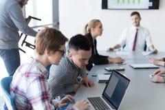 Молодые пары дела работая на компьтер-книжке, группе предпринимателей дальше Стоковая Фотография RF