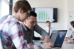 Молодые пары дела работая на компьтер-книжке, группе предпринимателей дальше Стоковое фото RF