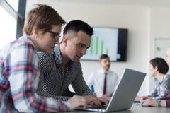 Молодые пары дела работая на компьтер-книжке, группе предпринимателей дальше Стоковое Изображение RF