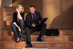 Молодые пары дела с компьтер-книжкой на шагах Стоковые Фотографии RF