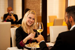 Молодые пары едят обедающий продукта моря на ресторане и выпивают вино Стоковое фото RF