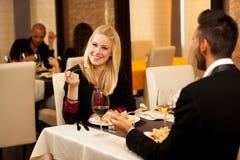 Молодые пары едят обедающий продукта моря на ресторане и выпивают вино Стоковая Фотография