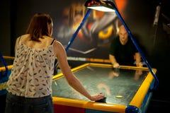 Молодые пары играя игру хоккея воздуха Стоковые Изображения RF