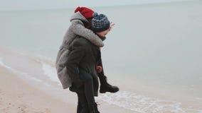 Молодые пары играя на пляже Водоворот человека и девушки сток-видео