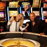 Молодые пары играя рулетку в казино держа пари и выигрывая Стоковые Фото