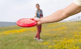Молодые пары играя frisbee Стоковые Фотографии RF