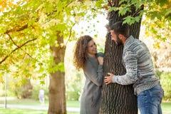 Молодые пары имея потеху в осенних древесинах, парах peeking от b Стоковое Изображение RF