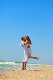 Молодые пары имея потеху на пляже Стоковые Изображения