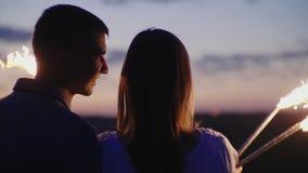 Молодые пары имея потеху с фейерверками Они смотрят вперед перед ими, фейерверками горят в их руках сток-видео