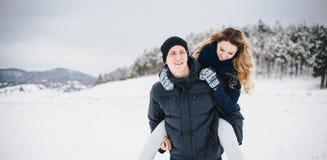 Молодые пары имея прогулку в снежной сельской местности Стоковое фото RF