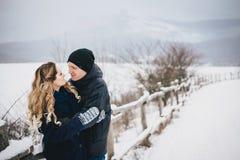 Молодые пары имея прогулку в снежной сельской местности Стоковые Изображения RF
