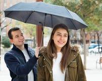 Молодые пары имея прогулку и усмехаться города Стоковые Фотографии RF