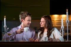 Молодые пары имея романтичный обедающий на обеденном столе дома стоковые изображения