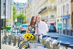 Молодые пары используя велосипеды в Париже, Франции Стоковые Изображения RF